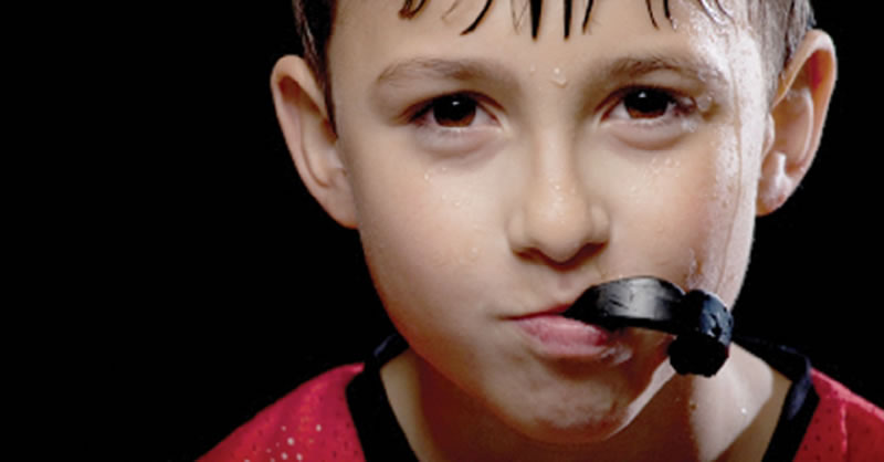 Woodtock dentist - Mouth Guards - boy with sports guard after hockey practice