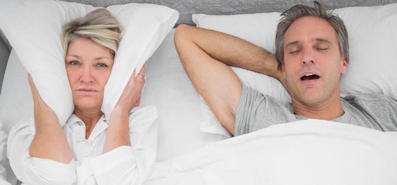 Woodstock Dentist - Snoring & Sleep Apnea - image of man snoring and wife covering ears